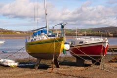 Vue plus étroite à marée basse rouge et jaune de bateaux de pêche Photo libre de droits
