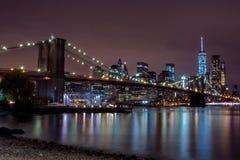 Vue pourpre de coucher du soleil de pont de Brooklyn et d'horizon inférieur de Manhattan Photos stock