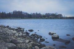 Vue régénératrice du lac large avec de l'eau bleu pierreux rivage et espace libre Passerelle au-dessus de fleuve Arbres près de l Photographie stock libre de droits