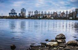 Vue régénératrice du lac large avec de l'eau bleu pierreux rivage et espace libre Passerelle au-dessus de fleuve Arbres près de l Photos stock
