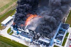 Vue a?rienne d'entrep?t industriel br?l? ou de b?timent central de logistique apr?s le grand feu avec de la fum?e ?norme du toit  images stock