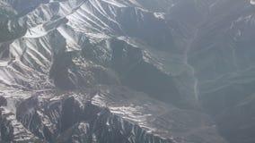 Vue a?rienne des montagnes neigeuses Vue de l'avion sur des plis d'une montagne Les dessus des montagnes couvertes de neige banque de vidéos