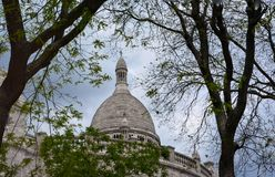 Vue of the Sacre Coeur dome, France. Sacre Coeur Basilica vue from below and surounded by trees , Montmartre district, Paris, France stock photography