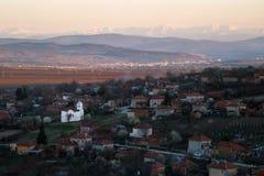 Vue scénique d'église de village de Slavyani avec la ville de Lovech à l'arrière-plan Gamme de balkan en Bulgarie, égalisant la l photographie stock libre de droits