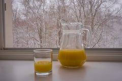 Vue scénique d'un verre et d'une cruche partiellement remplis avec le jus d'orange Photos stock
