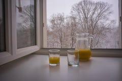 Vue scénique de glasse et d'une cruche partiellement remplie avec le jus d'orange Images libres de droits