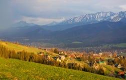 Vue scénique de village de Koscielisko avec le panorama de haut Tatras sur le fond, Pologne Photos stock