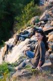 Vue scénique, fille s'asseyant sur des roches près d'une cascade Photos stock