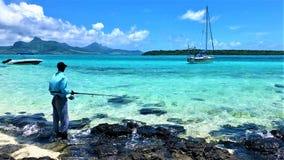 Vue scénique sur la lagune bleue îles Maurice de baie avec le pêcheur image libre de droits
