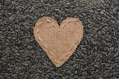 Vue sous forme de coeur fait de toile de jute avec des graines de tournesol Photos libres de droits