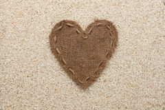 Vue sous forme de coeur fait de toile de jute avec du riz Photos stock