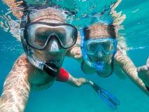 Vue sous-marine des couples naviguant au schnorchel photos stock