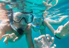 Vue sous-marine des couples naviguants au schnorchel en mer images libres de droits