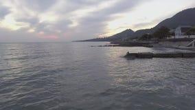 Vue stupéfiante de la Mer Noire, ligne de côte, colline verte au coucher du soleil avec le ciel nuageux clips vidéos