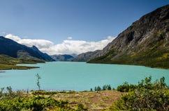 Vue stupéfiante du lac bleu en cristal Gjende en parc national de Jotunheimen avec de belles montagnes derrière et ciel bleu photos libres de droits