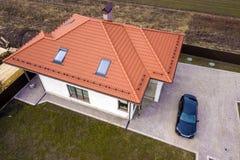 Vue supérieure aérienne de toit de bardeau en métal de maison avec les fenêtres de grenier et la voiture noire sur la cour pavée image libre de droits