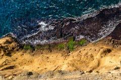 Vue supérieure aérienne des vagues de mer frappant des roches sur le rivage avec l'eau de mer de turquoise images libres de droits