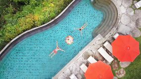 Vue supérieure aérienne : Les jeunes ajoutent au petit déjeuner de flottement dans la piscine L'homme et la femme nagent vers l'u image libre de droits