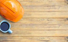 Vue supérieure avec le casque de sécurité et la tasse de café oranges sur le vieux bois Photographie stock libre de droits