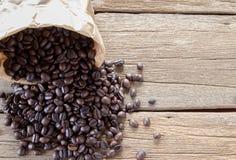 Vue supérieure avec les grains de café rôtis sur le fond en bois de table photographie stock libre de droits
