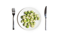 Vue supérieure blanche de foodon végétarien de régime Choux de bruxelles de bébé d'un plat avec la fourchette et le couteau Images stock