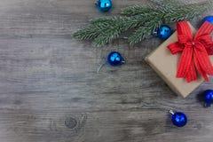 Vue supérieure, boîte-cadeau plat de configuration et ornement avec la branche de pin sur le fond en bois gris Photographie stock