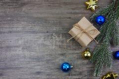 Vue supérieure, boîte-cadeau plat de configuration et ornement avec la branche de pin sur le fond en bois gris Photos libres de droits
