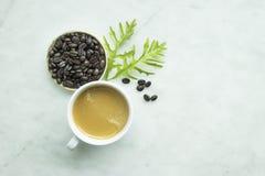 Vue supérieure, café frais haut fermé de tasse et avec le congé et les haricots Photo libre de droits