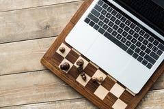Vue supérieure d'échiquier, d'ordinateur portable et de pièces d'échecs sur rustique photo stock