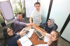 Vue supérieure d'équipe célébrer le succès dans la chambre de présentation avec des fenêtres et le conseil de présentation souria photo libre de droits