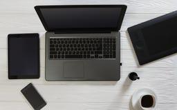 Vue supérieure d'articles de bureau sur le fond en bois - ordinateur portable et comprimé avec une tasse de café sur le bureau bl Photos libres de droits