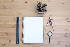 Vue supérieure d'artiste de lieu de travail Papeterie avec le carnet sur la table en bois Photos stock