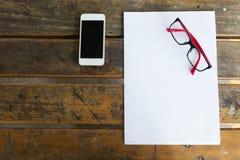 Vue supérieure d'espace de travail créatif avec le blanc et le mobile de livre blanc Image libre de droits