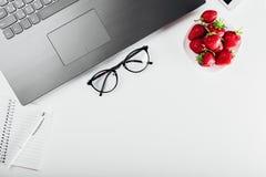 Vue supérieure d'espace de travail d'indépendant avec l'ordinateur portable, le carnet, le téléphone, les verres et le casse-croû Images libres de droits