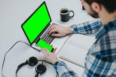 Vue supérieure d'homme d'affaires utilisant le smartphone et l'ordinateur portable Image stock