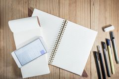 Vue supérieure d'objet fonctionnant : calculatrice ouverte APP de crayon gris et de smartphone blanc sur le carnet blanc à l'arri Photos libres de droits
