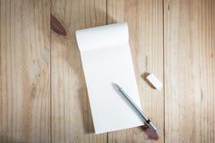 Vue supérieure d'objet fonctionnant : crayon gris sur le carnet et la gomme blancs sur la table en bois Photos stock