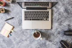 Vue supérieure d'ordinateur portable avec la tasse de café, l'écouteur, le carnet, le stylo et le cactus sur le fond grunge Image stock