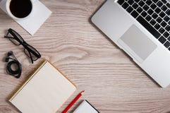 Vue supérieure d'ordinateur portable et de bloc-notes avec des verres et des écouteurs sur le bureau et la tasse de café en bois  Image libre de droits