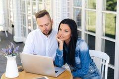 Vue supérieure d'un beau jeune couple se reposant à une table dehors, utilisant un ordinateur portable L'homme lit des sms à son  photographie stock libre de droits