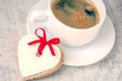 Vue supérieure d'un biscuit en forme de coeur avec le glaçage et le ruban rouge et d'une tasse de café au-dessus d'un fond rustiq Photographie stock libre de droits