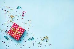 Vue supérieure d'un boîte-cadeau pointillé par rouge, des confettis en forme d'étoile éclatants dispersés et des rubans colorés a photo libre de droits