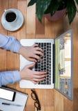 vue supérieure d'un bureau avec l'ordinateur portable (avec des mains d'affaires là-dessus), le carnet, les verres et le café Sur Images libres de droits