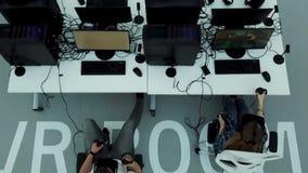 Vue supérieure d'un bureau moderne avec les spécialistes de essai en jeux en verres de réalité virtuelle, concept moderne de tech clips vidéos