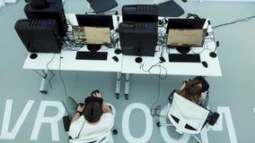Vue supérieure d'un bureau moderne avec les spécialistes de essai en jeux en verres de réalité virtuelle, concept moderne de tech banque de vidéos