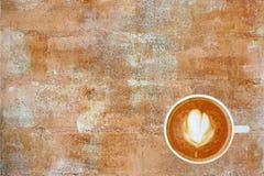 Vue supérieure d'un café avec le modèle de coeur dans une tasse blanche sur le fond rouillé de ciment, art de latte image stock