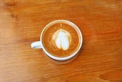 Vue supérieure d'un café avec le modèle de coeur dans une tasse blanche sur le fond en bois Image stock