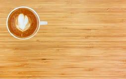 Vue supérieure d'un café avec le modèle de coeur dans une tasse blanche sur le fond en bois Images stock