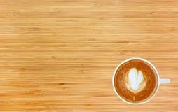 Vue supérieure d'un café avec le modèle de coeur dans une tasse blanche sur le fond en bois Photographie stock