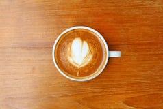 Vue supérieure d'un café avec le modèle de coeur dans une tasse blanche sur le fond en bois Photo libre de droits
